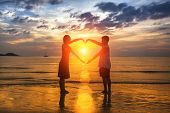 Silhouette of loving couple during an amazing sunset, holding hands in heart shape.