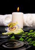 Spa Setting Of Passiflora Flower, Green Branch Fern, Towels And Candle On Zen Stones In Ripple Refle