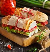 pic of sweetie  - Salami sandwiches with lettuce and sweety drop peppers on an old wooden board - JPG