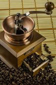 An old fashioned coffee grinder with coffee beans