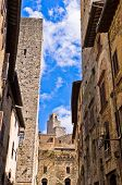 Medieval architecture of San Gimignano, towers and houses in narrow street, Tuscany