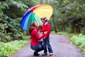Mother And Son Laughing Under A Colorful Umbrella