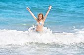 Young Woman Playing In Big Waves In The Ocean