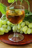glass of white wine with grapes on a wooden background