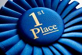 image of prize winner  - Blue first place winner rosette or badge from pleated ribbon with central text to be awarded to the winner of a competition on a graduated grey background with copyspace - JPG