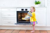 Curly Toddler Girl In Kitchen Mittens Next To Oven With Apple Pie