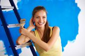 Happy beautiful young woman doing wall painting, standing near