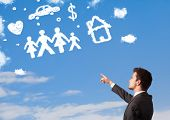 Businessman daydreaming with family and household clouds on blue sky