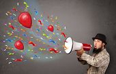 Young guy having fun, shouting into megaphone with balloons and confetti