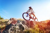 stock photo of rocking  - Mountain biker in action across rocks against blue sky concept for healthy lifestyle - JPG