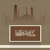 Arabic islamic calligraphy of text Eid-Ul-Adha with mosque silhouette on floral design decorated brown background.