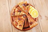 sweet food : apple pie cuts served on wooden plate over table with cinnamon and lemon