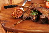 savory plate on wood : grilled ribs on plate with chives and tomato isolated on wooden table