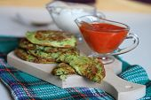 zucchini fritter with sour cream and hot pepper sauce