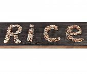The word 'rice' written of rice, on black wooden surface isolated on white background