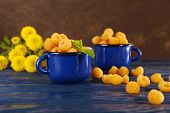 Yellow raspberries in dark blue mugs and wildflowers on wooden table on dark background