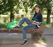 Attractive girl college student reading a book on bench in the park