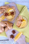 Glasses of ginger drink with lemon on napkin on cutting board on wooden background