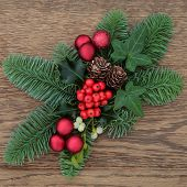 Christmas floral decoration with red baubles, fir, holly, ivy mistletoe and pine cones over oak wood