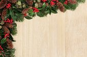 Christmas background  border with holly, ivy, fir leaf sprigs, pine cones over light oak background.