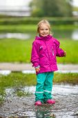Happy little girl stays in a puddle