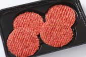 four raw hamburger patties on black plastic tray
