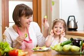 Mother And Child Girl Preparing Healthy Food And Having Fun
