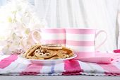 Two mugs of coffee with biscuits on napkin on table on white curtain background