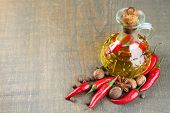 Homemade natural infused olive oil with red chili peppers and spices in glass bottle on  wooden back