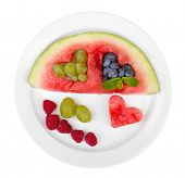 Fresh juicy watermelon slice  with cut out heart shape, filled fresh berries, on plate, isolated on
