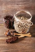 Glass jars and spoon of coffee beans on wooden background