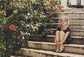 Cute Little Girl Is Sitting On The Stairs