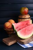 Composition of ripe watermelon, fruits, pink wine in glass and wooden barrel on color wooden backgro
