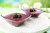 Delicious berry mousse in bowls on table on bright background