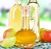 stock photo of cider apples  - Apple cider vinegar in glass bottles and ripe fresh apples - JPG