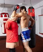 stock photo of muay thai  - Fighter exercising muay thai style elbow technique on a mannequin - JPG