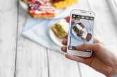 Hand making photo of sandwiches with flags on mobile phone for social network