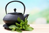 Chinese traditional teapot with fresh mint leaves on wooden table, on bright background