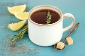 Cup of tasty herbal tea with thyme and lemon on blue wooden table