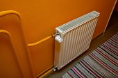 Heating radiator detail against orange wall