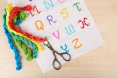 Handmade embroidered letters on white fabric and scissors on wooden background