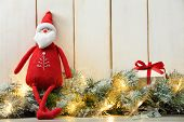 Cloth Santa Claus doll,Christmas lights and gift box on wood background.