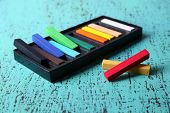 Colorful chalk pastels in box on color wooden background
