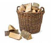 Wicker basket filled with firewood on a white background