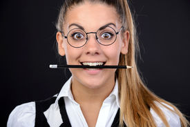 foto of nerd glasses  - Young nerd woman crazy expression in glasses holding a pencil in her mouth on black background - JPG