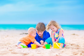 stock photo of spade  - Three kids teen age boy little toddler girl and a funny baby playing together digging in sand with colorful toys spade and buckets relaxing on a sunny tropical beach during family summer vacation - JPG