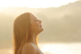 picture of deep  - Backlight profile of a woman breathing deep fresh air in the morning sunrise isolated in white above - JPG