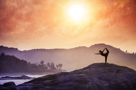 image of om  - Woman doing Yoga natarajasana dancer pose on the rocks at sunset at Om beach Gokarna India - JPG
