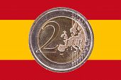 Common Face Of Two Euro Coin On Flag Of Spain