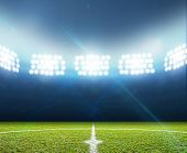 pic of illuminating  - A soccer stadium with a marked green grass pitch at night under illuminated floodlights - JPG